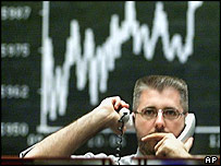 A broker using two telephones as he monitors markets