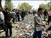 Iraqis walk among hundreds of shoes abandoned on Aima bridge