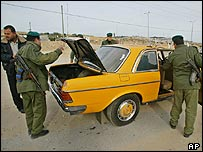 Palestinian police check a Palestinian taxi near the Erez crossing between Israel and the Gaza Strip