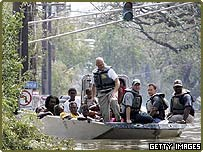 New Orleans residents are taken ashore in a boat after being rescued from their homes in high water