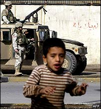A boy runs for cover as a US soldier disembark from a Humvee in Baghdad