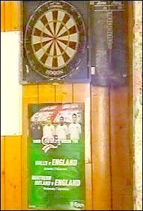 England poster under a Welsh dartboard