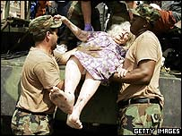 Elderly woman being helped onto truck