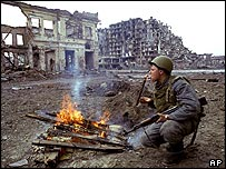 Russian soldier lights a cigarette amid ruins of Grozny March 1995
