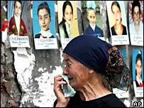 A woman cries as she looks at portraits of those killed in Beslan's School No 1