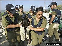 Israeli soldiers evacuate a Jewish settler