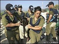 Israeli soldiers evacuate a Jewish settler