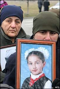 Relatives hold pictures of their dead, at the Beslan road protest