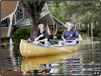 Tulane University employees paddle a canoe through the uptown section of New Orleans.