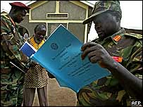 Sudanese People's Liberation Army (SPLA) soldiers look at a copy of the comprehensive peace agreement.
