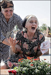 A Beslan teacher is overcome at the grave of one of her pupils