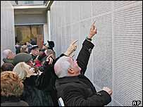 Visitors point to names engraved on the 