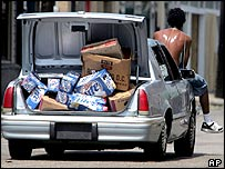 A man sits in a car with a boot full of looted beer
