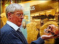 The museum's director, Jim Kennedy, inspects the replica Homo floresiensis skull