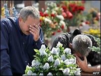 Мужчины рыдают на кладбище в Беслане 1 сентября 2005 года