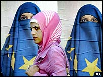 Turkish woman walks past poster of women wearing EU flag