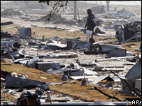 A military policeman looks for water containers along the debris strewn waterfront in Gulfport after Hurricane Katrina hit