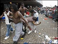 A woman is carried from a holding area after fainting at the Superdome, New Orleans