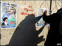 Posters for Iraqi election being plastered on wall