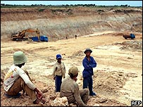Cambodian labourers look at bulldozers and trucks at a site in Phnom Penh, 08 July 2005.