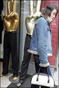 A woman walks past mannequins in the shape of the victory sign on a Beijing street