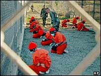 Detainees sit in a holding area at Camp X-Ray at Guantanamo Bay, Cuba, January 2002