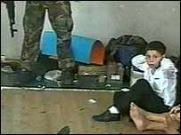 Scene from video footage made by the hostage-takers showing a gunmen pressing his foot on a detonator and a boy