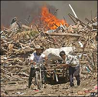 Two men remove their belongings as flames spread on the debris-strewn coast of Indonesia's tsunami-battered Aceh province , 25 Jan