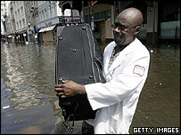 A man gathers his belongings in the wake of Hurricane Katrina in New Orleans