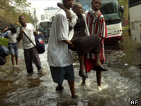 Survivors carry a woman along flooded streets of New Orleans