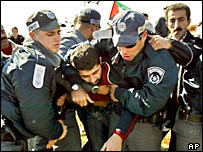 Israeli troops scuffle with a Palestinian demonstrator near Iskaka in the West Bank
