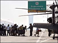 Survivors in New Orleans board an army helicopter near the Superdome