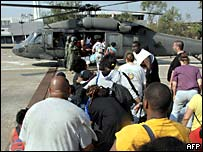 New Orleans survivors board an army helicopter near the Superdome