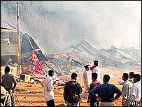 Indians standing by charred buildings at the temple complex