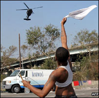 A stranded boy waves a white cloth at an army helicopter