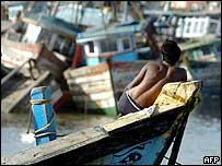 An Indian man rests on the top of a fishing boat in the port of a tsunami-hit fishing village outside Nagapattinam, India