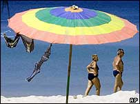 A Western couple walks past a parasol with a swimsuit hanging out to dry on Patong beach in Phuket, southern Thailand