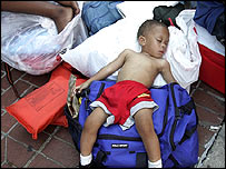 Young boy sleeping as he and his family await rescue
