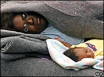 Mother sleeps with her young baby in Astrodome, Houston, Texas