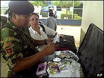 Un integrante de la guardia nacional de Venezuela examina el equipaje de una colombiana.