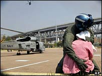 Helicopter crewman protecting a New Orleans evacuee from winds of landing chopper