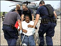 Man in wheelchair is helped on to helicopter
