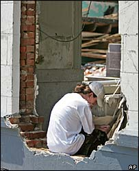 A woman sits in the rubble of a building in Hancock County, MS