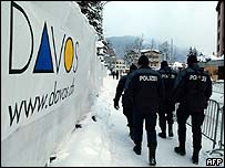 Policemen walk past a sign in Davos, the home of the World Economic Forum