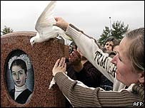 Girl places a dove on a gravestone in Beslan