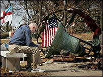 Man sits next to remnants of bell tower in Biloxi, Mississippi