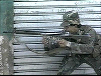 A soldier fires a gun during an attack on San Salvador