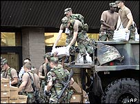 Soldiers unloading boxes of bottled water from a truck