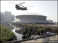 A Chinook helicopter hovers near the Louisiana Superdome