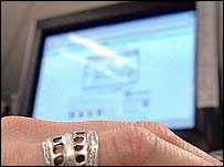 Adult's hand in front of a computer screen